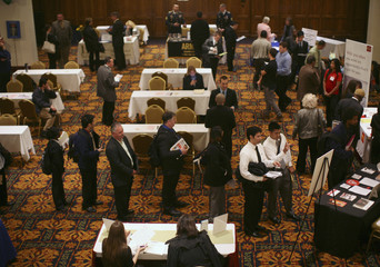 Job seekers stand in line to speak with employers at a job fair in San Francisco