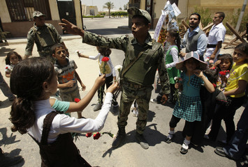 An Egyptian solider shouts at Palestinian children as they try to hand flowers to the soldiers during a rally at Rafah border crossing in the southern Gaza Strip