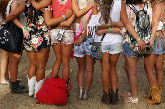 Country music fans in shorts and cowboy boots pose for a picture on the first day of the Stagecoach country music festival in Indio, California