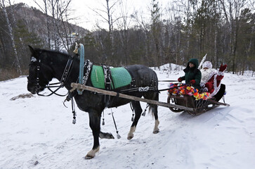 A man dressed as Father Frost sits on a sledge drawn by a horse as he arrives for a children's celebration at Father Frost's forest residence set up inside a local zoo in the Taiga district, outside Krasnoyarsk