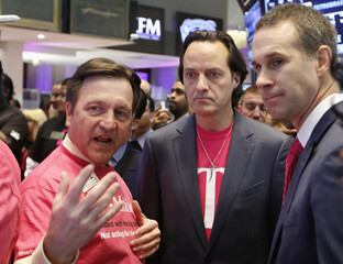 T-Mobile CEO John Legere looks on as a price is set for his company's shares before trading began on the floor at the New York Stock Exchange