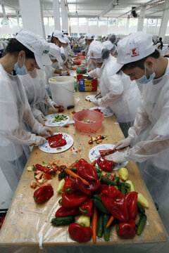 Volunteers cut vegetables to create the world's biggest vegetable salad during a Guinness World Record attempt in Pantelimon