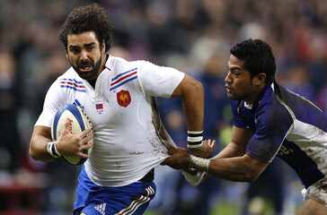 Samoa's Lilomaiava struggles with France's Huget during their rugby test match at the Stade de France stadium in Saint-Denis