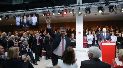 Former SPD leader Gabriel waves to the audience beside successor Schulz at a meeting of the Social Democratic Party (SPD) at their party headquarters in Berlin