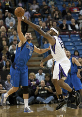Dallas Mavericks Stojakovic and Sacramento Kings Cousins battle for a loose ball during the first half of their NBA basketball game in Sacramento