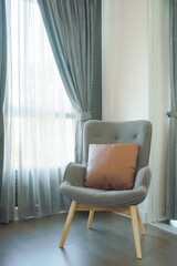 Stylish gray armchair with pillow in the living room