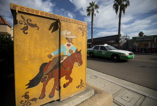 A taxi drives past a hand-painted utility box along the main street in the border town of San Ysidro, California