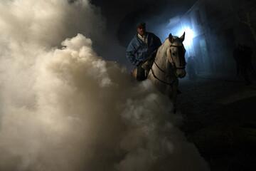 "A man and his horse prepare for the ""Luminarias"" annual religious celebration in San Bartolome de los Pinares"