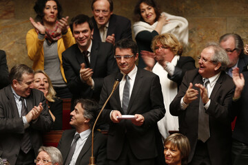 Deputies applaud French Socialist party deputy Erwann Binet, the rapporteur for the same-sex marriage draft law, at the National Assembly  in Paris