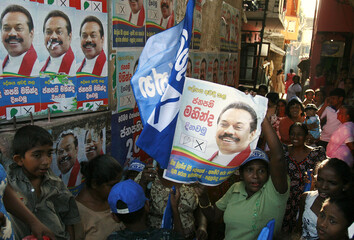 Supporters of incumbent President Mahinda Rajapaksa take shelter during a rally after police pushed them off the street while celebrating the closing of polls in Colombo