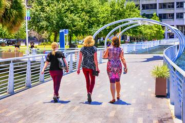 Three women walking along the Riverwalk in downtown Tampa FL