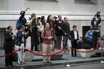 """Media stand on benches to photograph  Alibaba Group Holding Ltd founder, Jack Ma, in front of the New York Stock Exchange before the company's initial public offering (IPO) under the ticker """"BABA"""" in New York"""