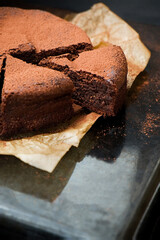 Chocolate flourless cake cut with cocoa powder. Dark food photography