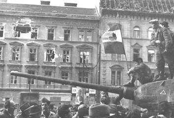 Fighters sit on top of a tank with a revolutionary flag in Budapest at the time of the uprising against the Soviet-supported Hungarian communist regime in 1956