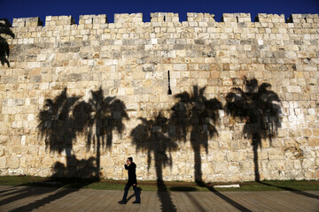 Palm trees cast their shadows on a wall surrounding Jerusalem's Old City as an Orthodox Jewish man walks past