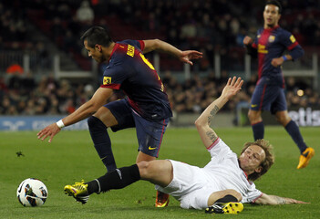 Barcelona's Sanchez fights for ball against Sevilla's Rakitic during their Spanish First division soccer league match at Camp Nou stadium in Barcelona