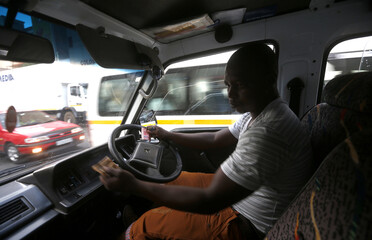 Minibus taxi driver Zakes Hadebe counts fares after making his first run of the day ferrying passengers from Soweto township to central Johannesburg
