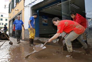 Men shovel mud out of a shop in downtown Funchal after heavy floods in Madeira island