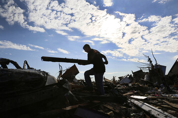 Jon Booth carries debris from his mother's tornado-destroyed home across the street from the Plaza Towers elementary school in Moore