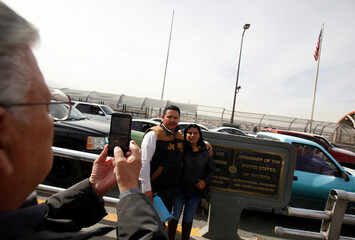 Justice of the Peace Avila takes a photograph of U.S. national Marquez and his bride Mexican national Venzor Mendoza after he married them on the Santa Fe international crossing bridge in Ciudad Juarez