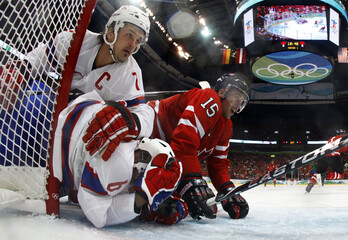 Holos and Jakogsen of Norway collide with Heatley of Canada during their hockey game at the Vancouver 2010 Winter Olympics
