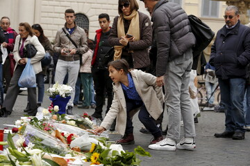Child places a flower, in sympathy with the victims of the Paris attacks, in front of the French embassy in Rome