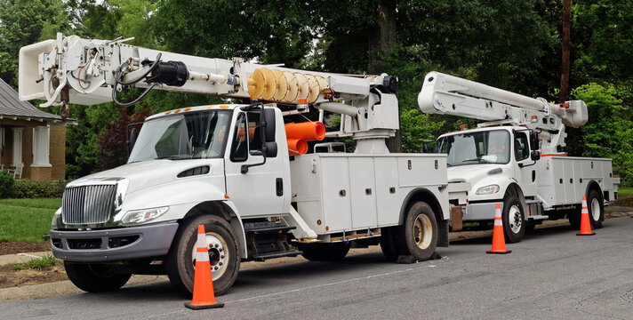 Front and side view of parked communication utility trucks in residential neighborhood. Horizontal.