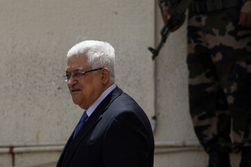 Palestinian President Abbas stands next to a security personnel officer after his meeting with U.S. Middle East envoy Mitchell in Ramallah