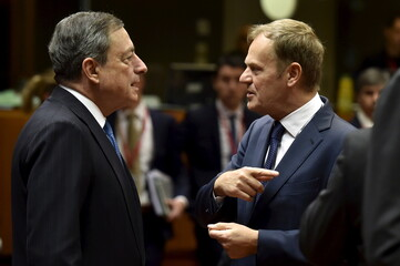 ECB President Draghi talks with European Council President Tusk during a European Union leaders summit in Brussels