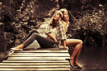 Two happy teen girls sitting on wooden bridge in summer forest