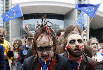 """Demonstrators, including members of the European Parliament, dressed as zombies, dance to the music of Michael Jackson's """"Thriller"""" while participating in a flash-mob in front of the EU Parliament in Brussels"""