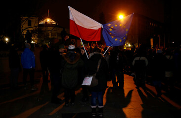 Demonstrators hold Polish and EU flags during a protest outside the Parliament building in Warsaw