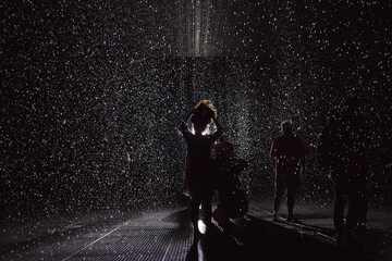 People stand in the new Rain Room installation at the Museum of Modern Art in New York