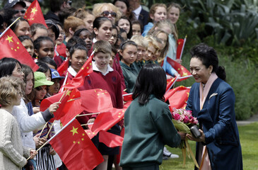 Peng Liyuan, wife of China's President Xi Jinping, receives a bouquet of flowers from schoolchildren as the couple receives a traditional Maori welcome upon arrival at the Government House grounds in Wellington