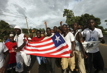 Supporters of Congress for Democratic Change (CDC) walk with a Lberian flag during their party's rally in Montrovia
