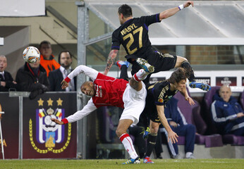 Poulsen of AZ Alkmaar collides with Wasilewski and Gillet of Anderlecht during their Europa League last 32 second leg soccer match in Brussels