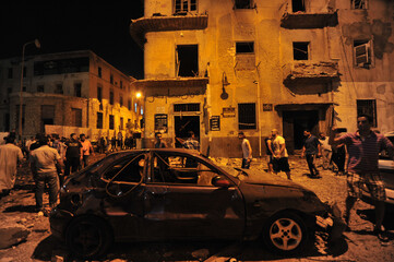 People gather to look at the damage caused by explosions at judicial buildings in Benghazi