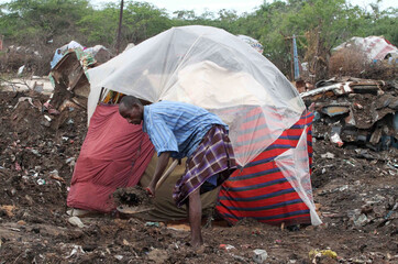 A displaced man from Somalia works in front of his makeshift shelter in south Mogadishu in Hodan district