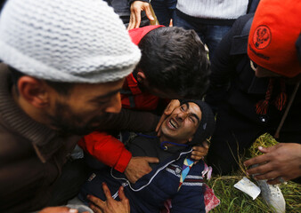 A migrant screams on the ground as migrants tried to cross the Greek-Macedonian border near the Greek village of Idomeni
