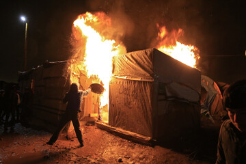 """A migrant attempts to extinguish flames from a burning makeshift shelter set ablaze in protest against the partial dismantlement of the camp for migrants called the """"jungle"""", in Calais"""