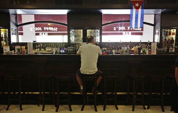A man sits at the bar in the newly reopened Sloppy Joe's bar in Havana