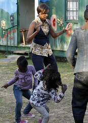 U.S. first lady Michelle Obama dances with children as she visits the Emthonjeni Community Center in Zandspruit Township