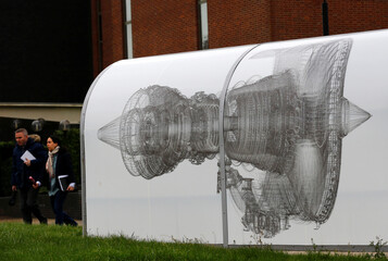 Workers walk past a shelter decorated with an image of an engine at a Rolls-Royce site in Derby