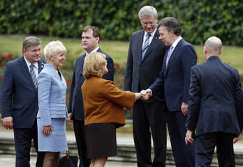 Colombia's President Juan Manuel Santos greets the delegation from Canada by Prime Minister Stephen Harper in Bogota
