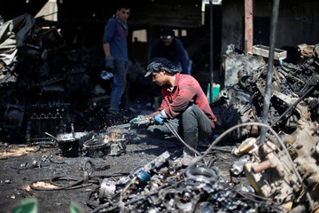 Workers cut car parts for the Jordanian graphic designer Abdelrahman Asfour, who turns car parts into furniture, at a junkyard in Amman