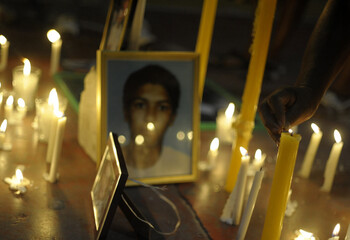 A person lights candles next to pictures of inmates during a vigil demanding justice from the government in front of the jail in Comayagua