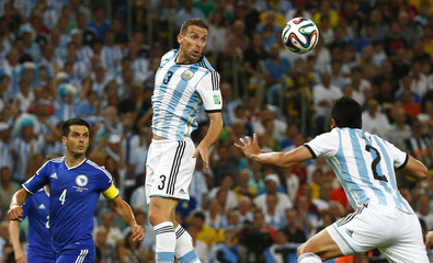 Argentina's Campagnaro reaches for the ball during their 2014 World Cup Group F soccer match against Bosnia at the Maracana stadium in Rio de Janeiro