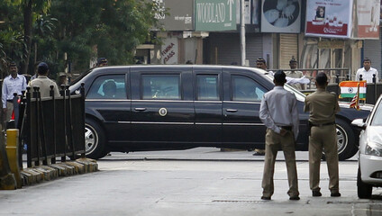 Policemen stand guard as a car from the motorcade of US President Barack Obama passes by in Mumbai