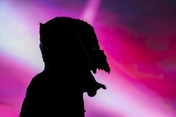 A person wearing a large mask is silhouetted against a screen at the West Hollywood Halloween Costume Carnaval, in West Hollywood, California