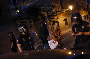 A demonstrator reacts as a police officer writes her ID during a protest in Madrid